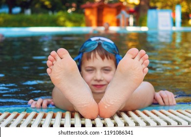 Cute child hanging his feet out of the swimming pool