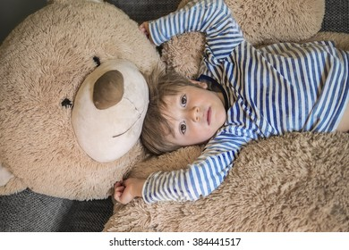 Cute child hanging out with his giant teddy bear