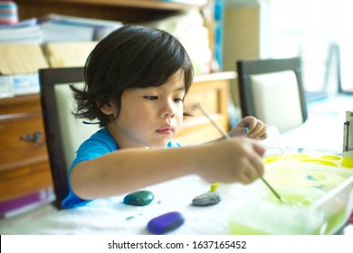 Cute child holding brush to paint on rocks.Asian boy having fun stone painting activity at home.Homeschooler's project.Learning art.Artistic artwork on stones.Young kid focusing on creative education.