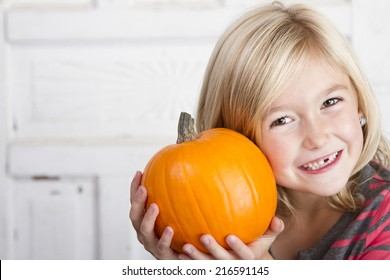 Cute child holding small pumpkin up by her face