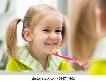 cute child kid girl brushing teeth in bathroom