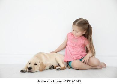 Cute child with Labrador Retriever at home