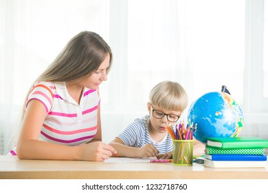 Cute child learning a lesson with his mother. Family doing homework together. Mothe explaining to her little schoolboy how to do a task.