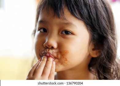 cute child licking a chocolate in her finger