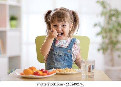 Cute child little girl eating healthy food in kindergarten