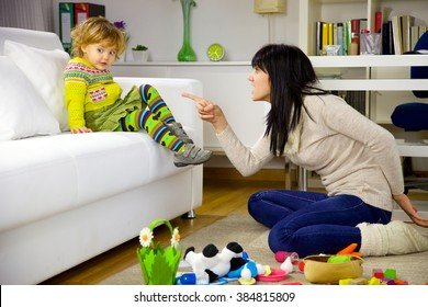Cute child making funny face while mother is angry