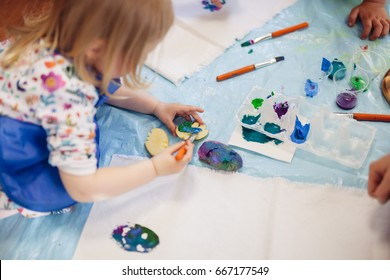 A cute child mixing colorful pots of acrylic paint and painting on the cloth. Eco dyeing