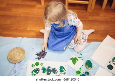 A cute child mixing colourful pots of acrylic paint and painting on the cloth. Eco dyeing
