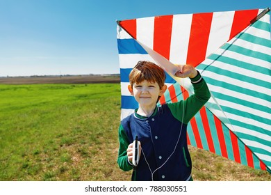 Cute child playing with a flying kite in meadow on sunny day.