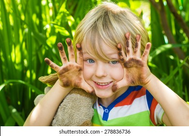 Cute child playing in garden with dirty hands