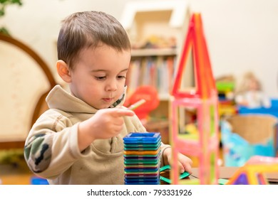 cute child playing with magnetic constructor toy