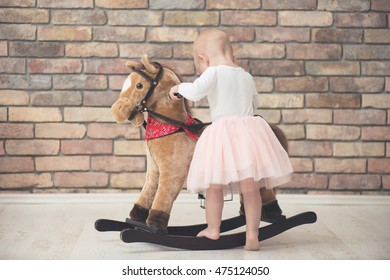 cute child playing with rocking horse