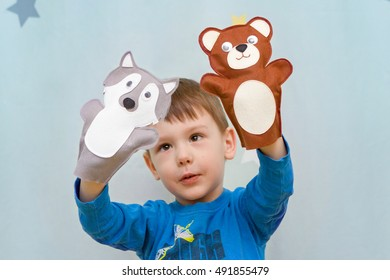 Cute child playing in the theater with hand puppet wolf and bear
