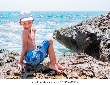 Cute child posing on sea beach. Holiday vacation family concept