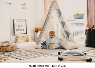 Cute child reading a book, laying on the pillows in stylish scandinavian tent in playroom