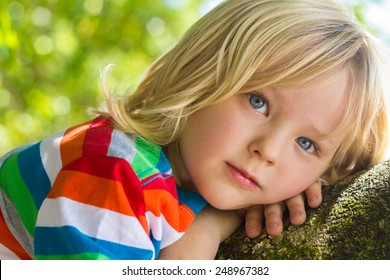 Cute child relaxing deep in thought outdoors on a tree