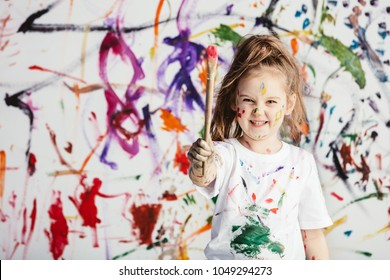 Cute child with smuges of colorful paint showing a paint brush. Little artist.
