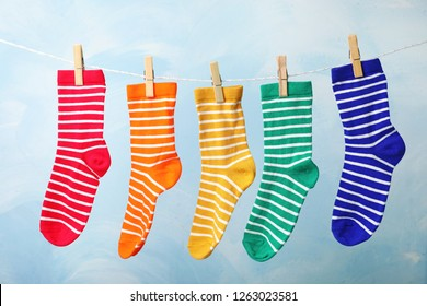 Cute child socks on laundry line against color background