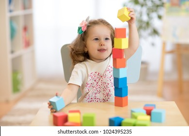 Cute child stacks building cubes sitting at table in nursery room