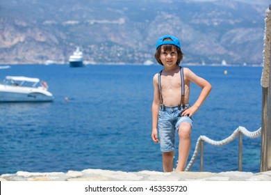 Cute child, standing on a path around Mediterranean sea on French riviera, enjoying sunny summer afternoon