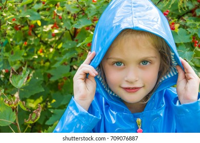 Cute child standing in the park in blue raincoat. Children's bright fashionable blue jacket for the little girl ,raincoat.Spring autumn, fashion, trendy clothing.Copy space
