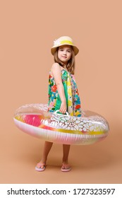 Cute child in sundress and straw hat with  swimming ring playing in studio