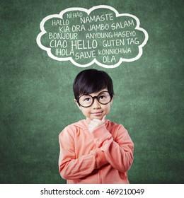 Cute child in thinking pose imagine multi language in the classroom