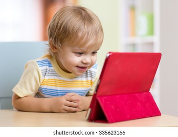 Cute child toddler boy with tablet pc sitting at table in home