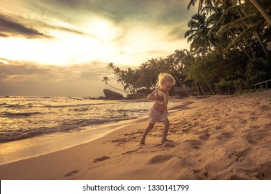 Cute child toddler walking on sunset beach during summer vacation concept happy childhood travel lifestyle