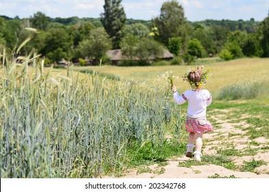 Cute child walking with flowers near wheat field in summer