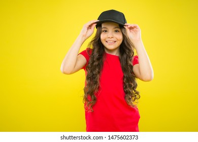Cute child wear cap or snapback hat. Little girl wearing baseball cap. Summer sun protection cap. Girl long curly hair wear cap. Must have street style accessory trends. Modern fashion. Kids fashion.