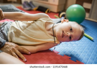 cute childe with cerebral palsy has musculoskeletal therapy by doing exercises on floor mat