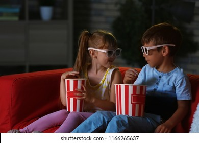 Cute children in 3d glasses watching movie on sofa in evening