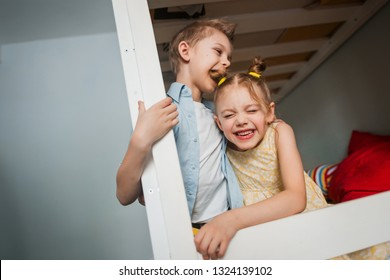 cute children 7-8 years old, brother and sister, play on the bed, the boy bit the girl by the hair, for her beautiful tails, the girl wrinkles and smiles