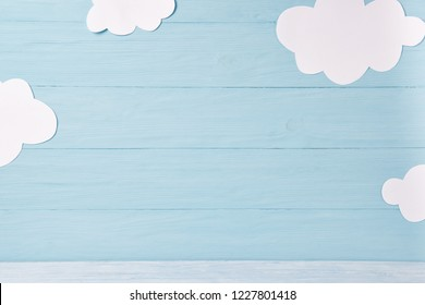 Cute children or baby background, white clouds on the blue wooden background