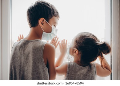 Cute Children Boy and Girl in medical Mask stay Home on Quarantine. Children play Home. Entertainment for the Children during quarantine. Self isolation. Children are looking out the window.
