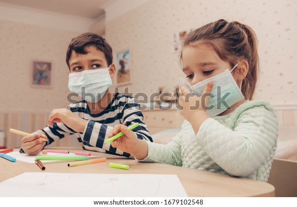 Cute children boy and girl in medical mask is sitting at home in quarantine. Сhildren play constructor after disinfection hands.  Entertainment for the children during  quarantine. Self isolation.