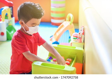 Cute children boy playing indoor  playground  with face mask protection. Children from kindergarten playing on playground. Self isolation.