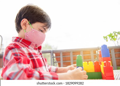 Cute children boy playing in terrace building blocks with face mask protection. Self isolation from covid-19 virus