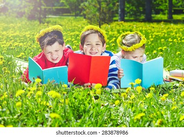 Cute children in dandelion wreaths reading on lawn