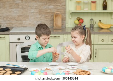 Cute children decorate cookies at a table in the home kitchen