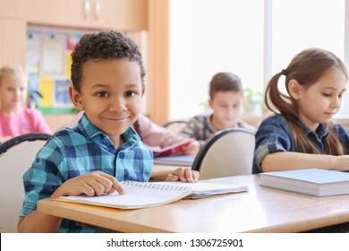 Cute children doing homework in classroom at school