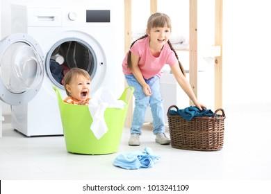 Cute children doing laundry indoors