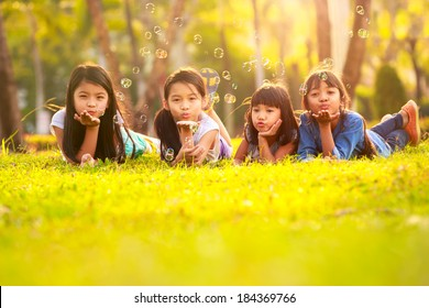 Cute children having bubble fun on green lawn in park
