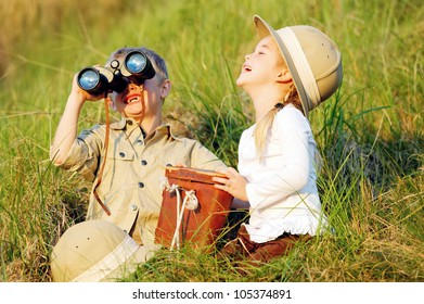 Cute children having fun and laughing together outdoors with binoculars and safari hats
