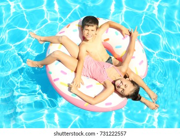 Cute children on inflatable ring in swimming pool