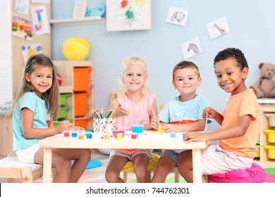 Cute children painting at table indoor