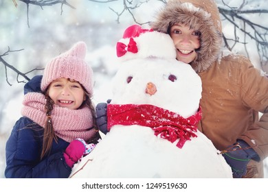 Cute children playing with snowman outdoors