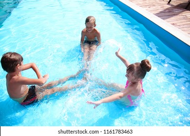 Cute children playing in swimming pool on summer day