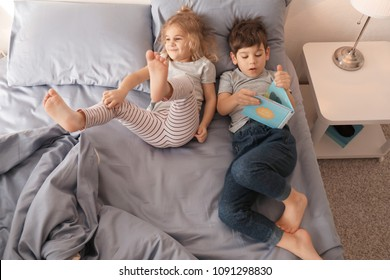 Cute children reading bedtime story on bed at home